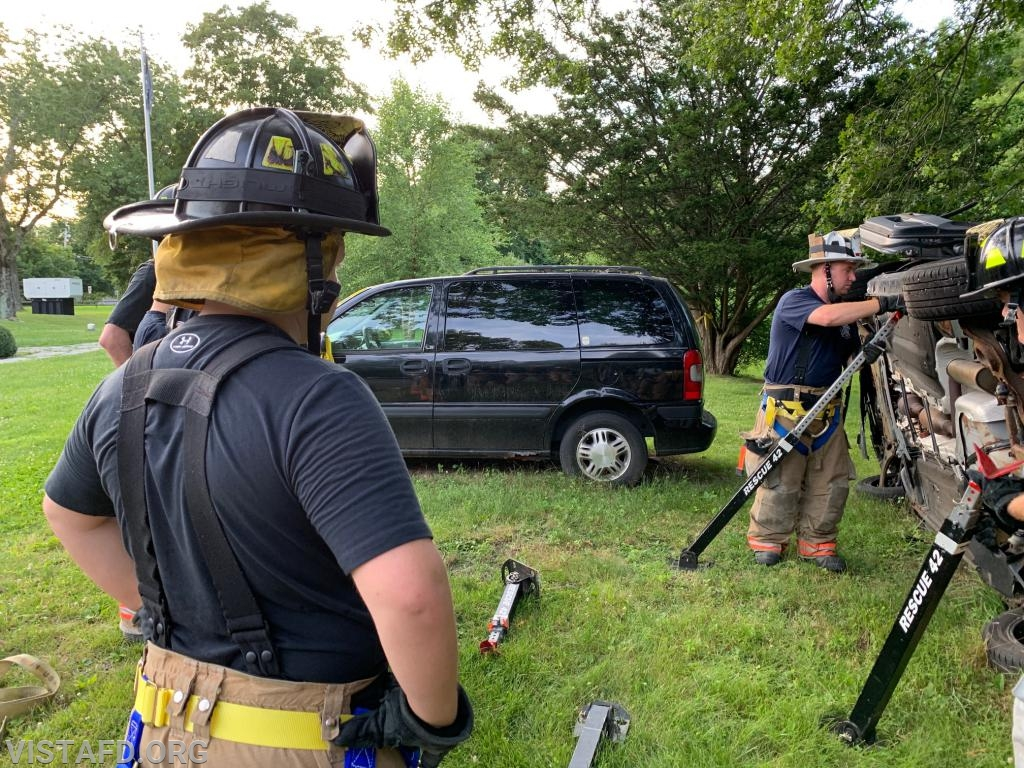 Vista Firefighters reviewing how to stabilize a car on it's side while it's leaning up against an object