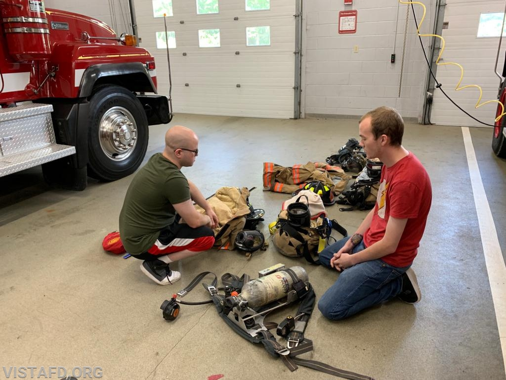 Firefighter Ryan Ruggiero going over gear and equipment with Probationary Firefighter Arlington Trenck