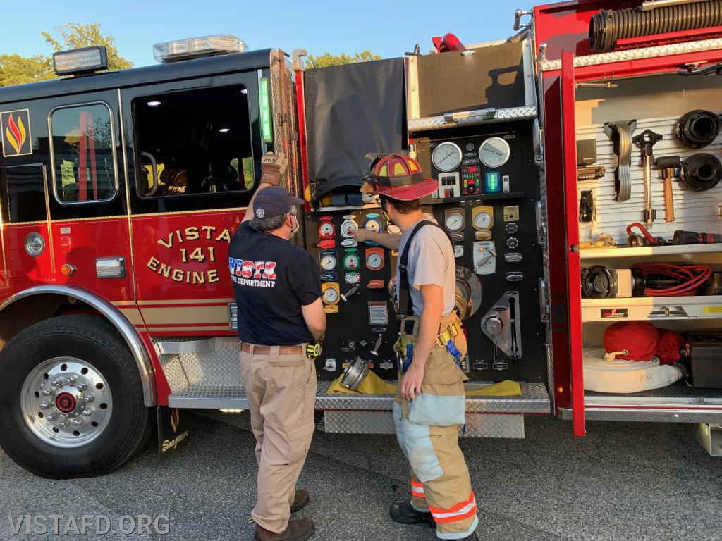 Capt. Brian Porco going over how to pump Engine 141 with Firefighter Brian Sferra