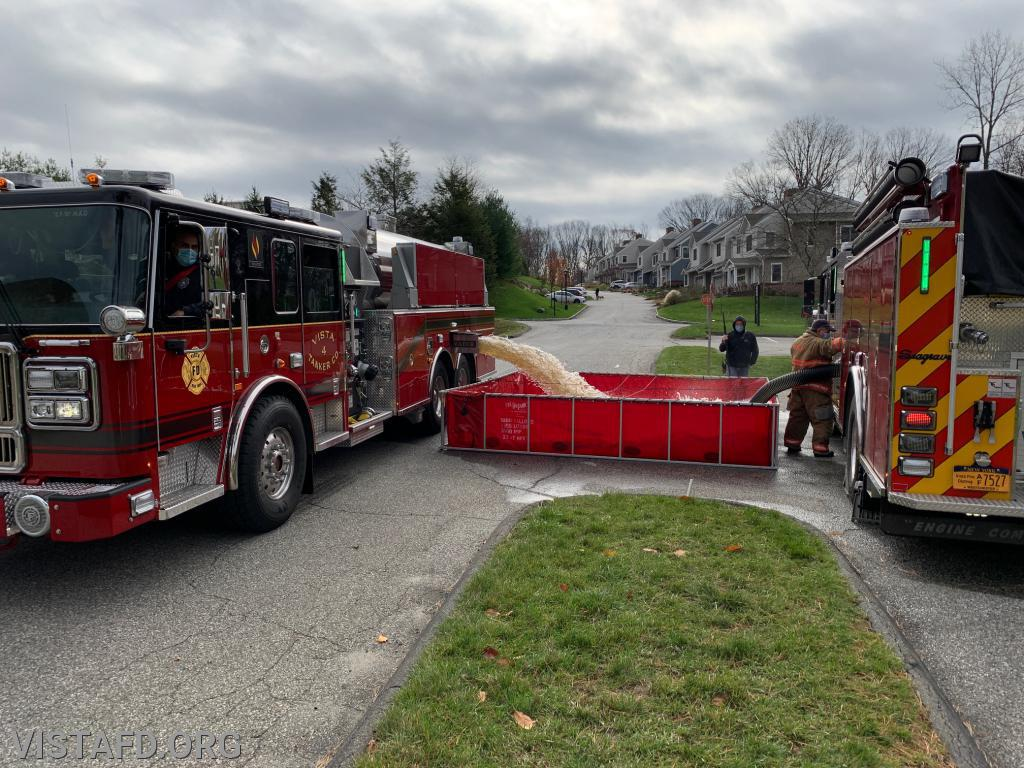 Tanker 4 dumping water into the portable pond as Engine 141 is conducting drafting operations
