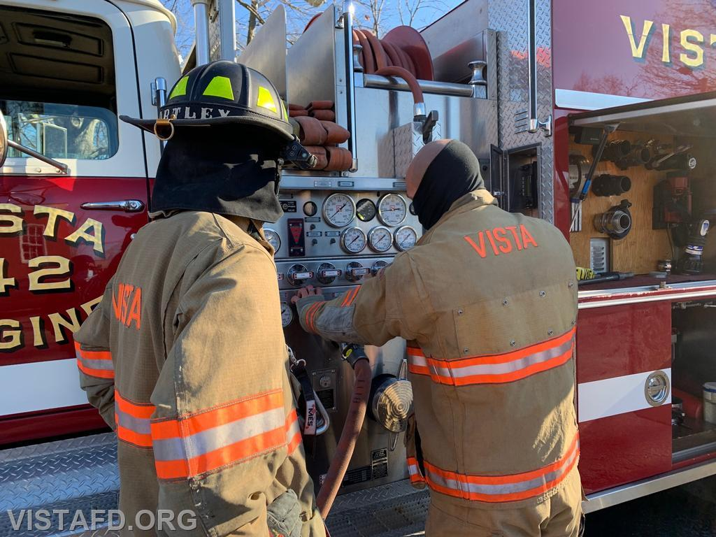 Lead Foreman Bartley and Probationary Firefighter Rosa going over how to operate the Engine 142 pump panel