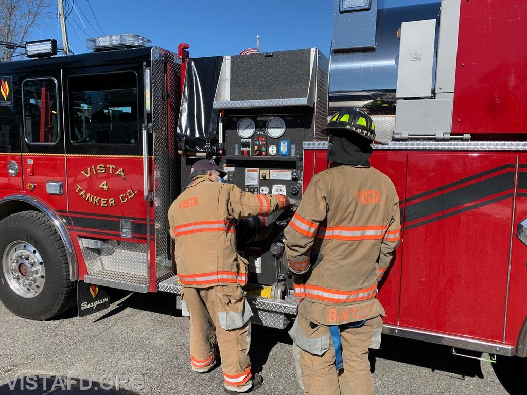 Firefighter Brian Sferra operating the Tanker 4 pump panel as Lead Foreman Adam Bartley looks on