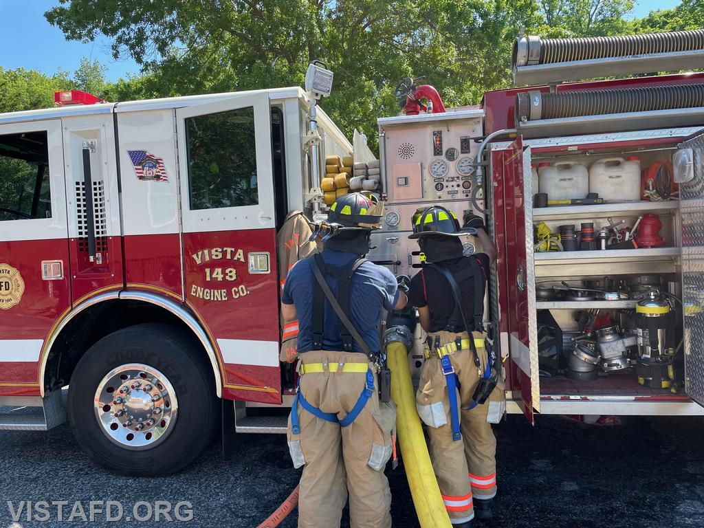 Firefighter Lance Phillips operating the Engine 143 pump panel as Foreman Dan Castelhano looks on