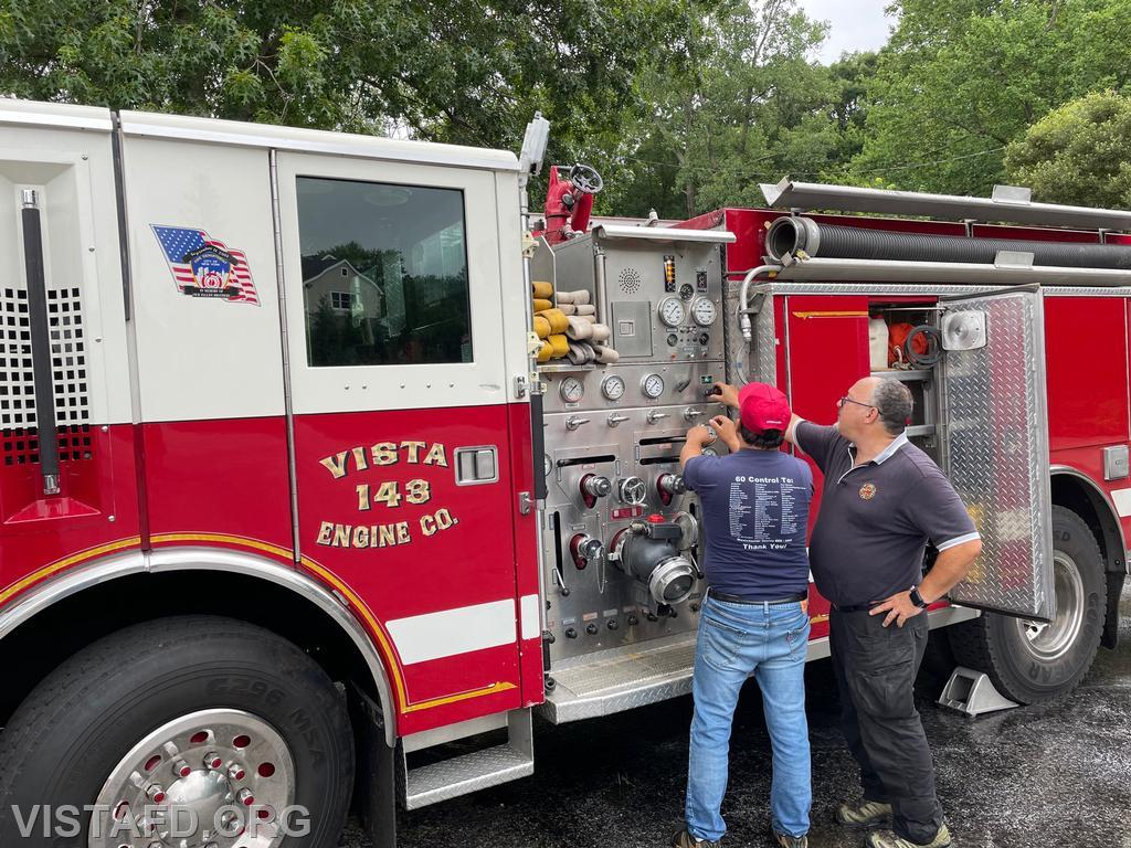 Firefighter Martin Rojas operating the Engine 143 pump panel as Firefighter/EMT Candidate Mark Albert looks on