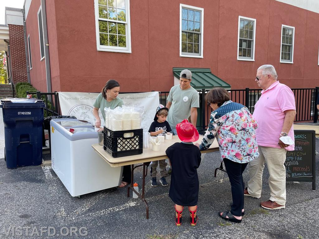 """Members of the community visiting """"The Farmer's Grind"""" ice cream stand"""