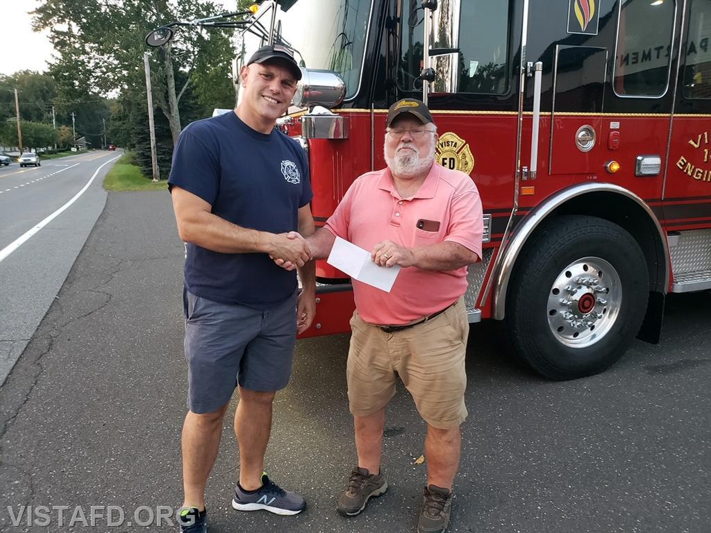 Lieutenant Marc Baiocco presenting the check to purchase the Onatru flag pole to Chairman John Lemke of the Lewisboro Town Veterans Advisory Committee