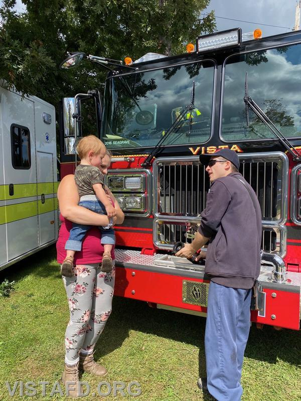 Firefighter Dom Mangone going over Engine 141 with members of the community