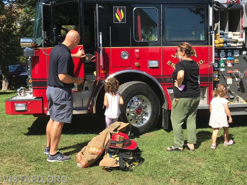 Lieutenant Marc Baiocco going over Engine 141 with members of the community
