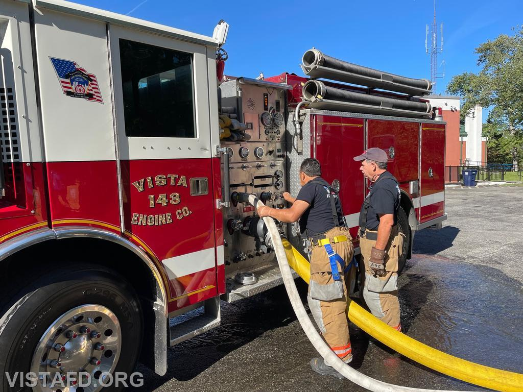 Firefighter Martin Rojas operating the Engine 143 pump panel as Foreman Brian Sferra looks on