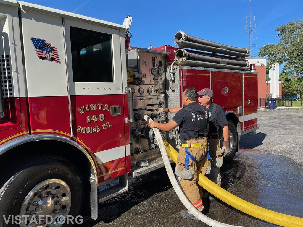 Foreman Brian Sferra going over the Engine 143 pump panel with Firefighter Martin Rojas