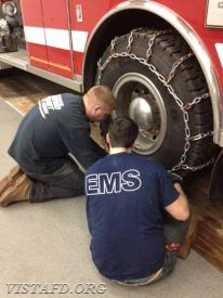 (L-to-R) Lt. Mike Peck and Probationary FF Jake Melcher place chains on Engine 141