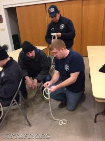 Capt. Mike Peck shows Foreman Adam Bartley and FF Martin Rojas how to do a knot