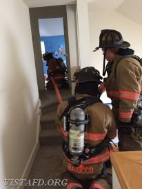 "Vista Firefighters advancing the 1-3/4"" hose line into the bedroom as Capt. Mike Peck observes"