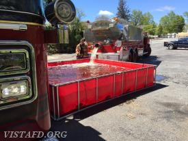 Foreman Jake Melcher dumping water from Tanker 4 into the portable pond