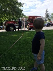 "Junior Firefighter Michael Fisher watching the hose line demonstration during ""VFD Family Fun Day"""