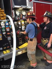 Lt. Brian Porco practices operating the Engine 141 pump panel as Capt. Mike Peck looks on