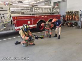 "FF Ryan Ruggiero and Probationary FF Finn Brannan performing the ""2-minute drill"" as Lt. Phil Katz checks gear"