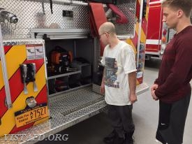 FF Ryan Ruggiero and Probationary FF Finn Brannan go over the tools & equipment on Engine 141