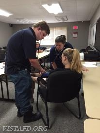 FF/EMT Candidate J.T. Bowensmith practices taking blood pressure as Lt. Allie Fisher listens