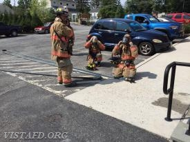 "Vista Firefighters practice 1-3/4"" hose line advancement as Lt. Phil Katz looks on"