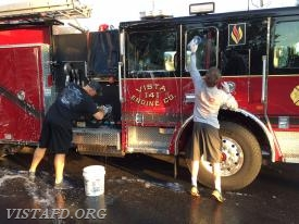Lead Foreman Marc Baiocco and Probationary FF Finn Brannan cleaning Engine 141