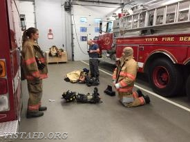 Foreman Castelhano showing Probationary FF/EMT Candidate Buzzeo how to put on Firefighting gear