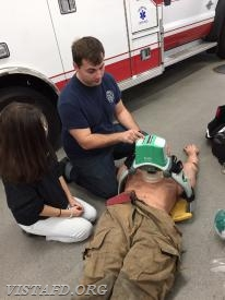 "Foreman Canil showing Probationary EMT Candidate Lilly how to operate the Lucas CPR machine during ""EMT Fundamentals Class"""