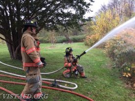 "Firefighter Ryan Ruggiero practices operating the 1-3/4"" fog nozzle as Lead Foreman Marc Baiocco looks on"