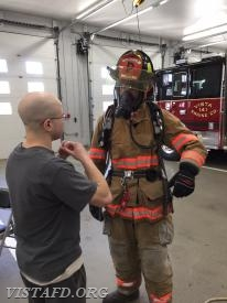 "Firefighter Ryan Ruggiero checking FF Sean Kaplan's gear following completing of the ""2-minute drill"""
