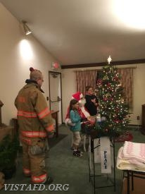 Santa greeting children from the Vista Fire District as Firefighter Ryan Ruggiero looks on