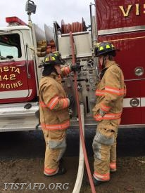 Foreman Mike Canil going over how to operate the Engine 142 pump panel with FF Patrick Healy