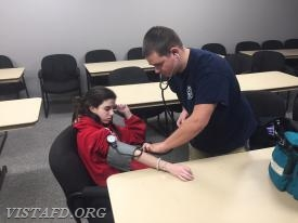Probationary EMT Candidate Nicholas Kaplan practicing how to take a blood pressure