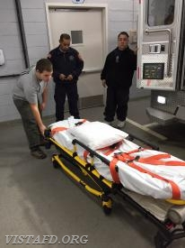 Probationary EMT Candidate Nicholas Kaplan learning how to use the power stretcher on Ambulance 84B1