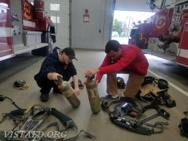 FF Dom Mangone and Probationary FF Peter Sloan inspecting an SCBA