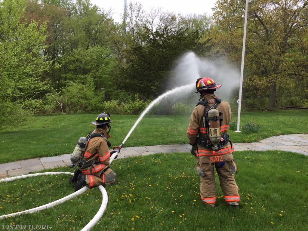 """Firefighter Healy operating the 2-1/2"""" hose line as Lt. Katz looks on"""