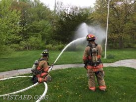 "Firefighter Healy operating the 2-1/2"" hose line as Lt. Katz looks on"