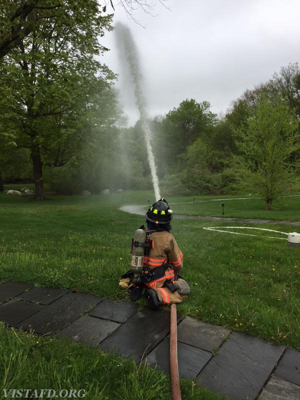"""Firefighter Ruggiero operating the 1-3/4""""' hose line"""