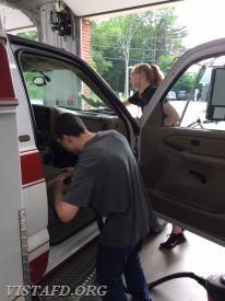 Ex-EMS Lieutenant Michel Behringer and EMT Candidate Isabel Fry cleaning Ambulance 84B2