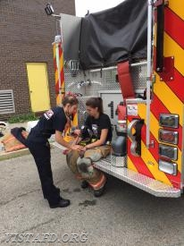 Probationary FF/EMT Candidate Elly Hersam helping with rehab operations during live fire training