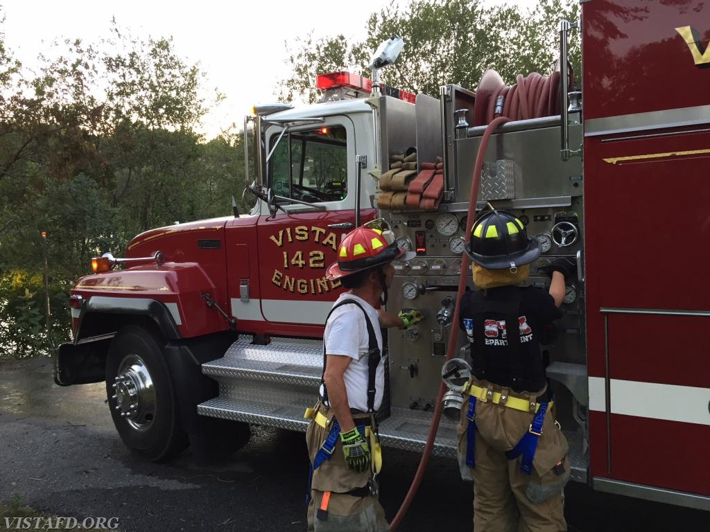 Firefighter Olivia Buzzeo learning how to draft water on Engine 142 as Lt. Phil Katz looks on
