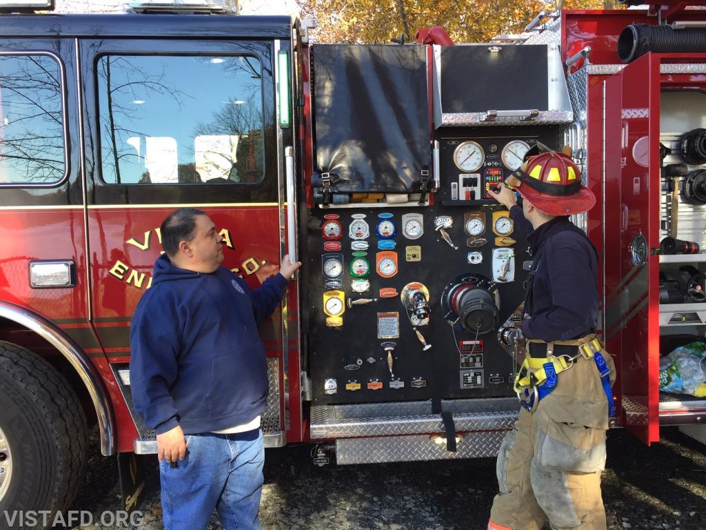 Capt. Brian Porco and Mutual Responder Dave Jacobsen operating the Engine 141 pump panel