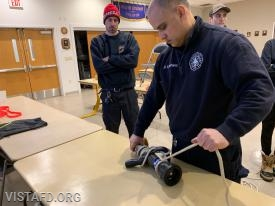 """Foreman Dan Castelhano practicing hoisting an 1-3/4"""" hose line with ropes & knot"""