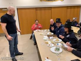 Lead Foreman Marc Baiocco of Platoon 1 presenting their meal to the cooking competition judges
