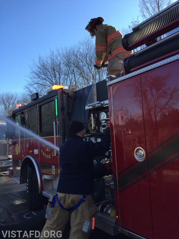 Capt. Brian Porco operating the deck gun while Foreman Mike Canil pumps Engine 141