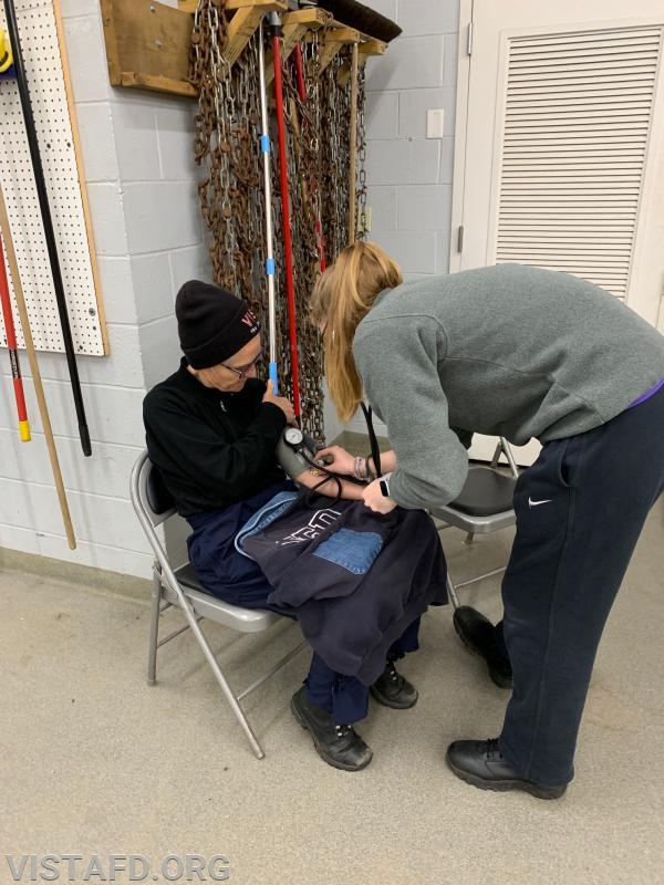 EMT Isabel Fry checking Firefighter Lynda Scott's vitals