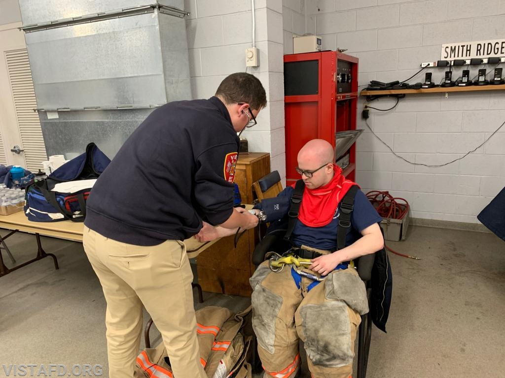 EMT Mark Sfreddo checking Firefighter/EMT Ryan Ruggiero's vitals